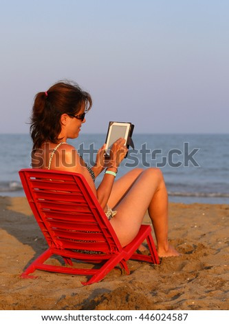 Pretty woman on red chair reads the ebook on the beach by the sea in summer