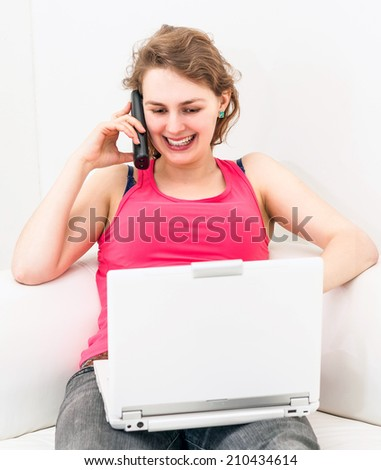 Pretty woman on the couch, using her laptop and talking on the telephone - stock photo