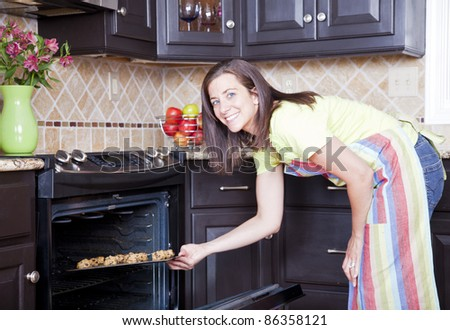 Pretty woman opening oven with a tray of cookies - stock photo