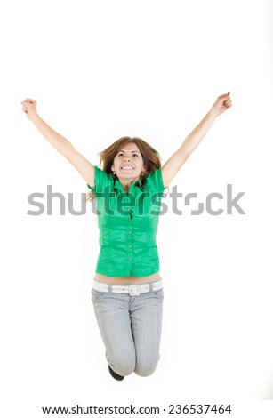 Pretty woman or girl jumping  with raised arms up of joy excited isolated on white background in green shirt and gray jeans and looking up. Model smiling. Photo of sure success and belief in yourself
