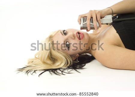 Pretty woman or girl music singer lying down with microphone on white - stock photo
