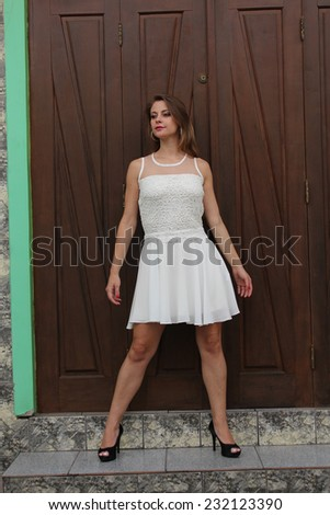 Pretty woman posing on a rustic wooden door - stock photo