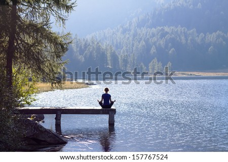 Pretty woman practicing yoga at a lake - stock photo