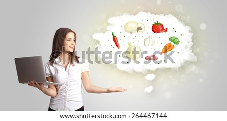 Pretty woman presenting a cloud of healthy nutritional vegetables concept - stock photo