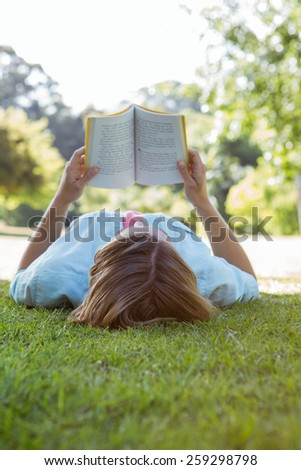 Pretty woman reading book in park on a sunny day - stock photo