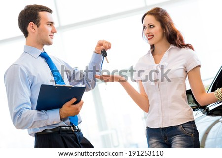 Pretty woman receives the keys to a new car from a sales manager - stock photo