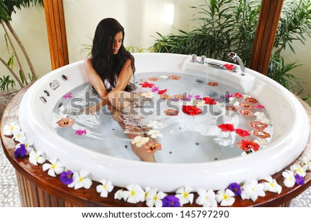 Pretty woman relaxing in jacuzzi with flower petals - stock photo
