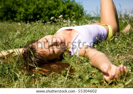 Pretty woman relaxing on a meadow in the green grass - stock photo