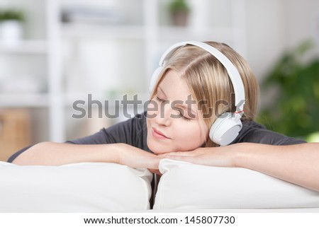 Pretty woman relaxing on a sofa in the living room listening to music on a set of headphones with her eyes closed in bliss