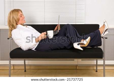 pretty woman relaxing with laptop on couch drinking coffee