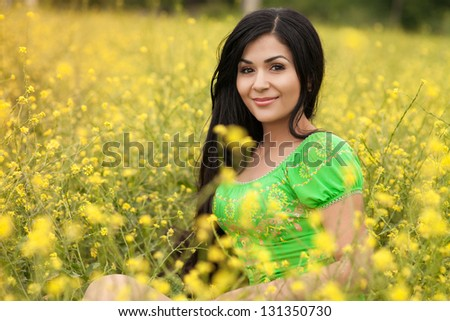 Pretty woman resting in blossom spring garden with field flowers on nature looking happy smiling outdoors. Brunette girl on grass in park engoying life. Attractive indian woman in country summer dress - stock photo