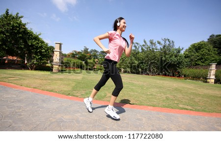 pretty woman running outdoors training at park with earphone - stock photo