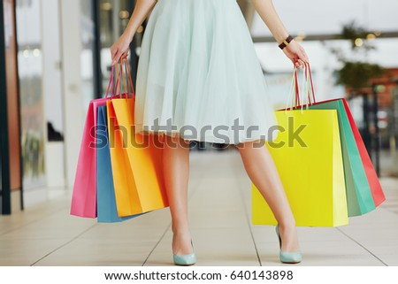 Pretty woman's legs wearing light dress and hills, holding colorful shopping bags in two hands, standing in shopping mall, shopping concept.