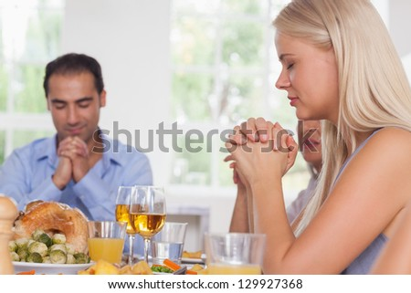 Pretty woman saying grace with family before thanksgiving - stock photo
