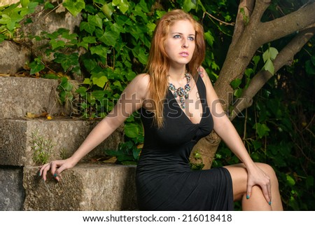 pretty woman seated on the stairs - stock photo