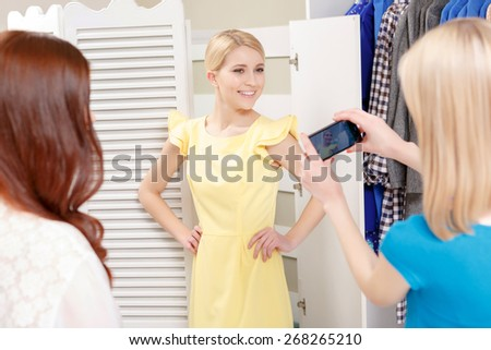 Pretty woman. Selective focus on a pretty young female shopper in a new dress being photographed by her friends in a fashionable boutique - stock photo