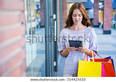 Pretty woman shopping at the mall on a sunny day - stock photo