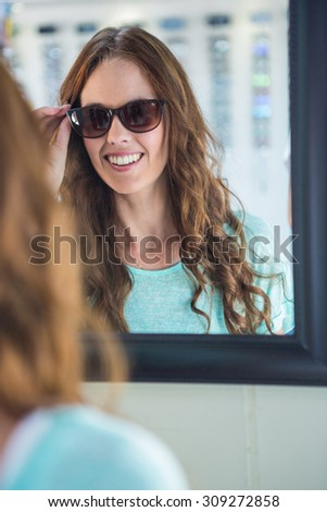 Pretty woman shopping for sunglasses at the optometry store