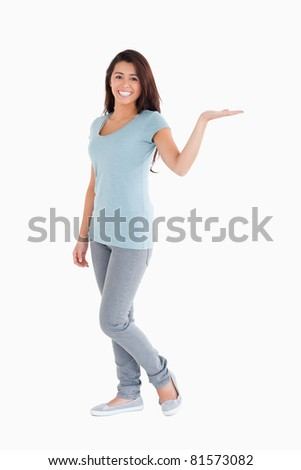 Pretty woman showing a copy space while standing against a white background