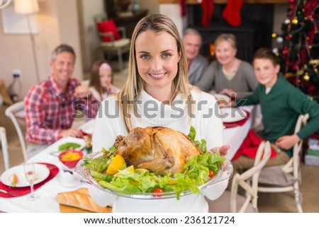 Pretty woman showing the roast turkey in front of her family at home in the living room - stock photo