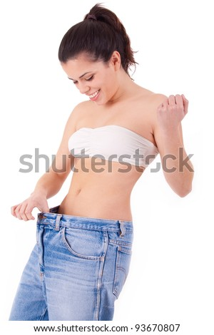 Pretty woman shows her weight loss by wearing an old jeans, isolated on white background - stock photo