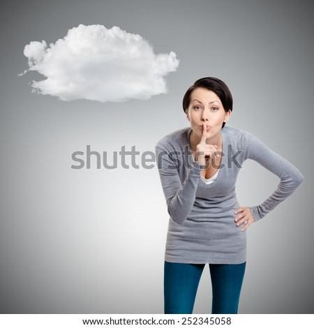 Pretty woman shows silence gesture with forefinger, isolated on grey background with cloud - stock photo