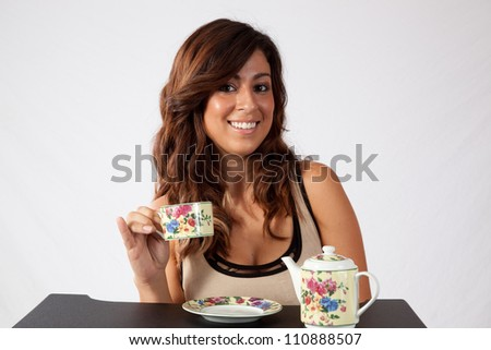 Pretty woman sitting and enjoying a cup of soothing tea from a flowered tea cup.