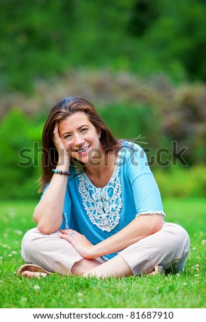 Pretty woman sitting on grass smiling portrait