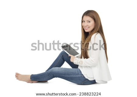 Pretty woman sitting on the floor and holding a digital tablet against a white background - stock photo