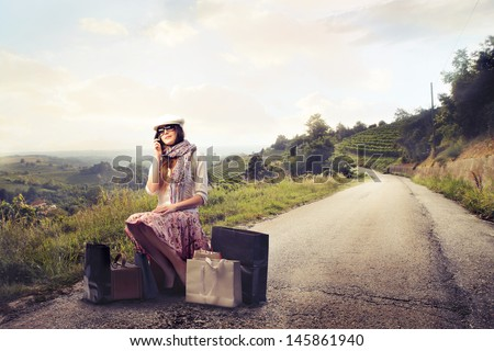 pretty woman sitting on the suitcases in a desert road - stock photo