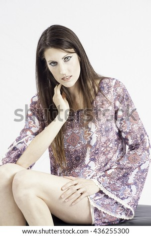 Pretty woman sitting thoughtfully in a dress  with eye contact