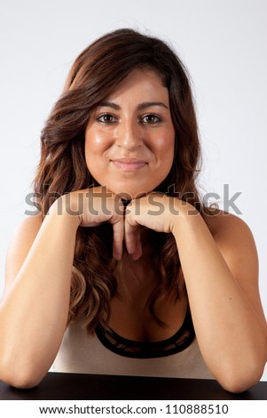 Pretty woman sitting with her chin in her hands, and a happy, friendly smile for the camera - stock photo