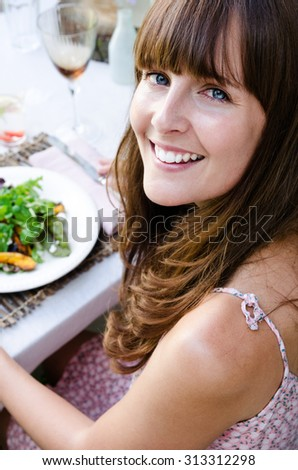 Pretty woman smiing over her shoulder while eating and enjoying her healthy organic mixed greens salad in a outdoor casual dining setting