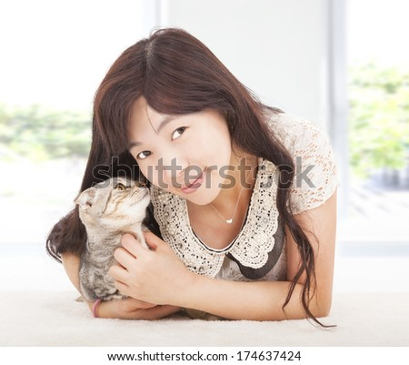 pretty woman smiling and hug her cat - stock photo