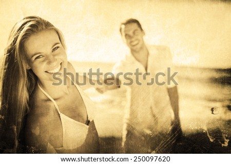 Pretty woman smiling at camera with boyfriend holding her hand against grey background - stock photo