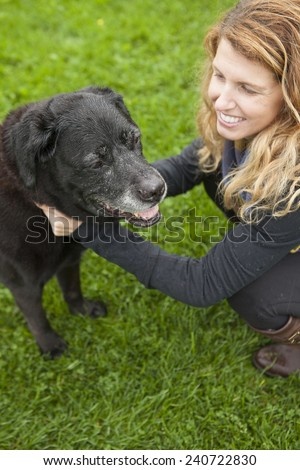 Pretty woman spending time with her aging dog    - stock photo