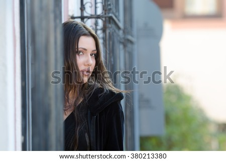 Pretty woman standing behind of a traditional window with iron bars, horizontal photo
