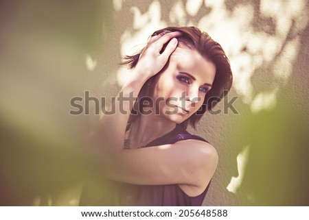 Pretty woman standing in shadow of tree