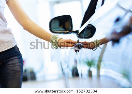 Pretty woman standing near car at car center. Choosing a car - stock photo