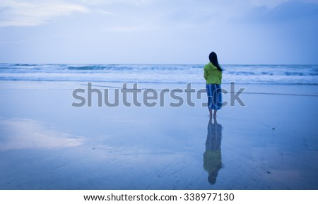 Pretty woman standing on the beach, overlooking the distant as if thinking - stock photo