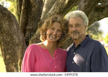 pretty woman stands with her handsome father. - stock photo