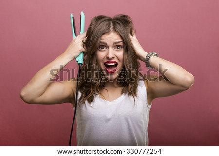 Pretty woman styling her hair with a curling iron - stock photo