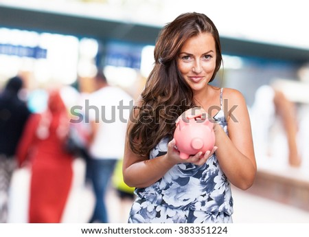 pretty woman taking care of her piggy bank - stock photo