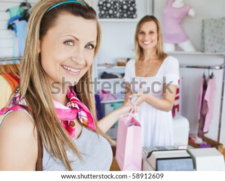 Pretty woman taking shopping bag smiling at the camera in a shop