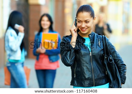pretty woman talking on the mobile phone, outdoor on the street - stock photo