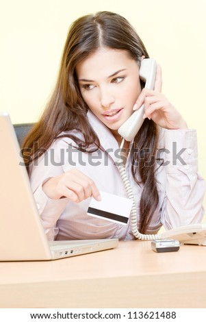 Pretty woman talking over phone, holding credit card and looking at the laptop - stock photo