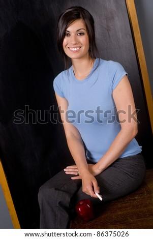 Pretty Woman teaching class teacher sits on desk by apple and blackboard - stock photo