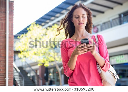 Pretty woman texting at the mall on a sunny day