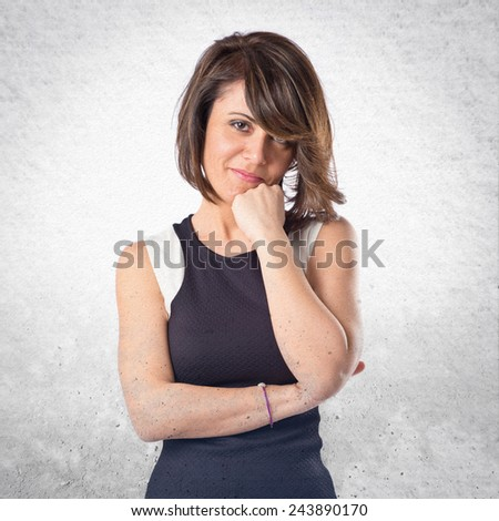 Pretty woman thinking an idea over textured background  - stock photo