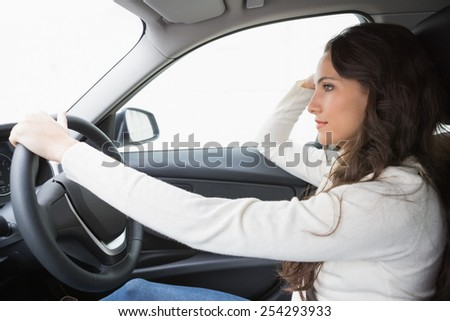 Pretty woman thinking and driving in her car